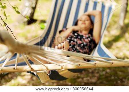 Young woman lying in a hammock in summer day. Outdoor relax.