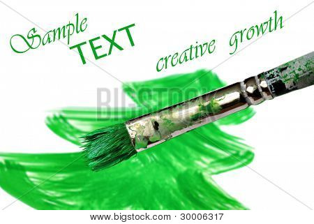 Well worn artist's brush being used by a student to paint a simple tree  - symbolizing creative growth.  Macro on white background with shallow dof and copy space.
