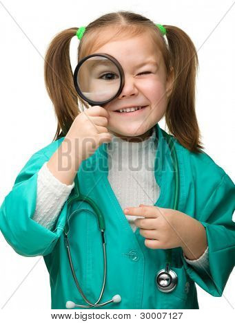 Cute little girl is playing doctor looking through magnifier, isolated over white