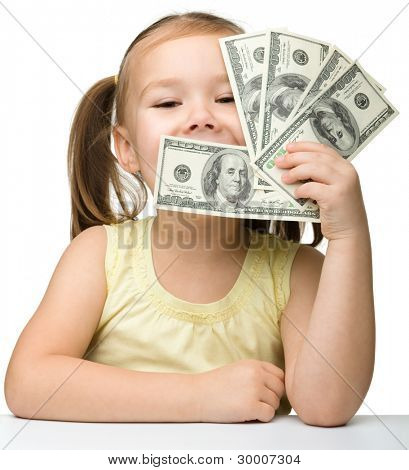 Cute little girl is covering her eyes with dollars, isolated over white