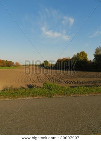 Fall Field Plowed Rows In Michgian At Sunset With Blue Skies And Whispy Clouds.
