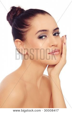 Portrait of young beautiful woman with clear make-up touching her face, over white background