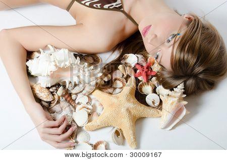 Young girl in bikini lays with seashells
