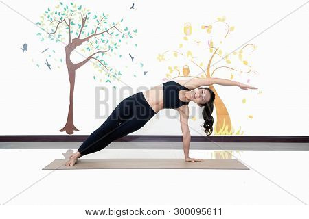 Healthy Women Practicing Yoga In Gym . Standing Stretching In Tree Pose,concept For Exercising And H