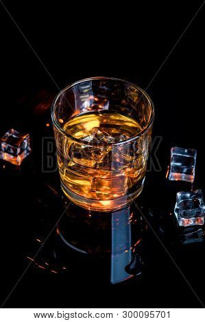 Whisky, Whiskey Or Bourbon In Glass With Ice Cubes On Black Reflection Background
