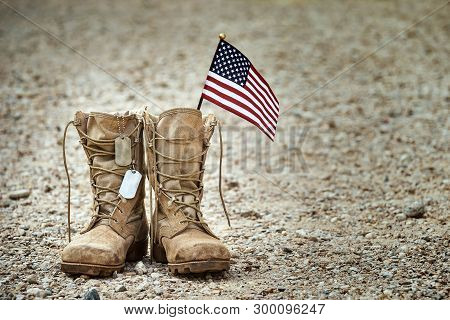 Old Military Combat Boots With Dog Tags And A Small American Flag. Rocky Gravel Background With Copy