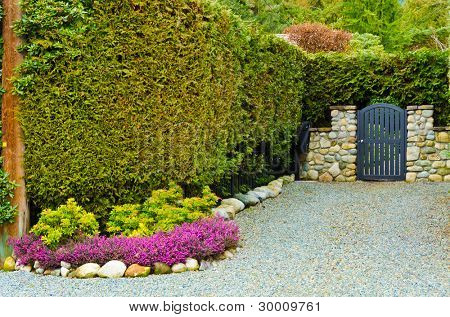 Beautiful gate over fantastic outdoor landscape with stone wall in Vancouver, Canada.