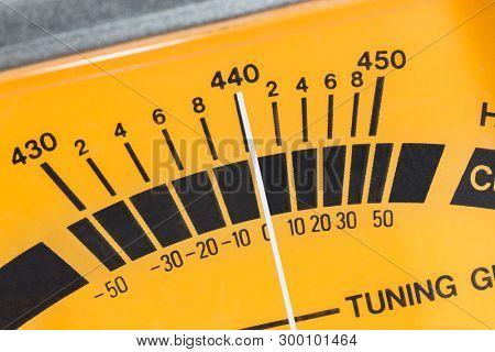 Macro close up detail of calibration meter on old guitar tuner.