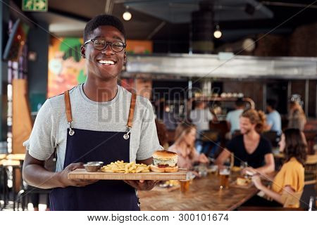 Portrait Of Waiter Serving Food To Customers In Busy Bar Restaurant