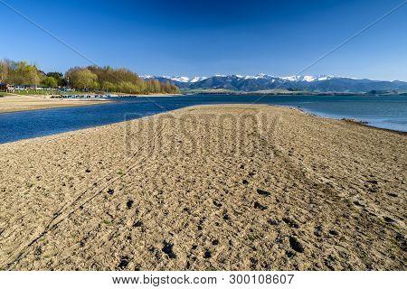 Dry Soil And Water Reservoir Liptovska Mara, Slovakia. Low Tatras Mountains At Background