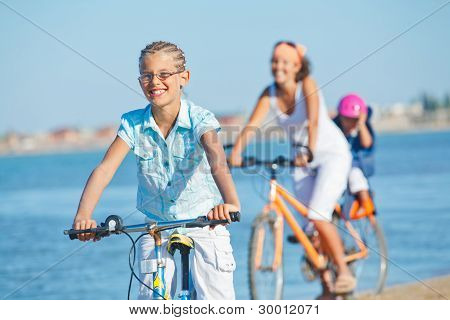 Cute girl with her mother and brother ride bikes