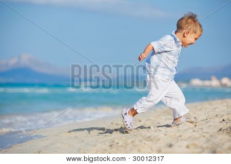 Young cute boy playing happily at pretty beach