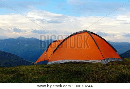 Orange tent in the mountains summer.