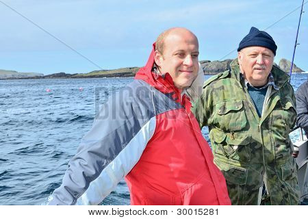Two fishermen - father and son - on boat