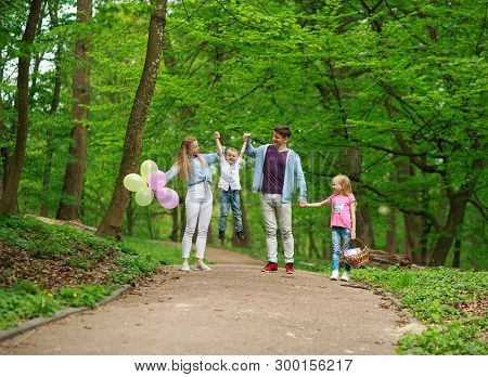 Family Father And Mother With Two Kids A Son And Daughter Walking In The Summer Green City Park On A