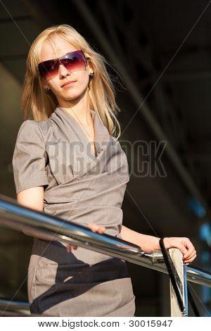 Beautiful Woman In Gray Dress Near The Shop