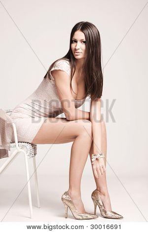 elegant young woman in short dress and high heels, studio shot