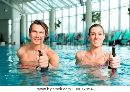 Fitness - a young couple (man and woman) doing sports and gymnastics or water aerobics under water in swimming pool or spa with Nordic walking sticks poster