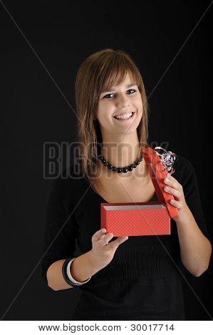 Teenager Opening A Red Present For Her Birthday