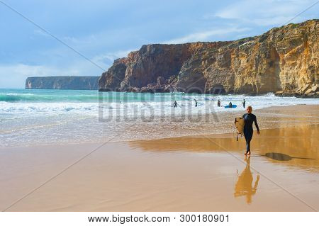 Sagres, Portugal - October 30, 2018: Young Man Walking By Sandy Beach With Surfboard. Algarve Is A F