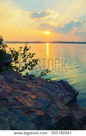Summer sunset landscape - stone cliff and lake lit by gold sunset summer light. Colorful summer landscape sunset scene