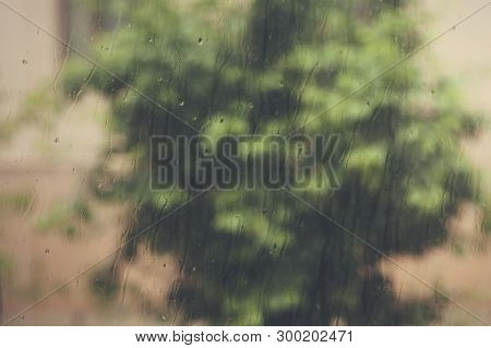 View To Raining Weather Through The Home Window. Raindrops On The Window Glass. Heavy Raining Outdoo