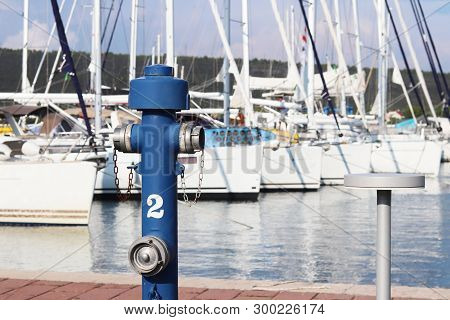 Hydraulic Fire-fighting Crane Of Blue Color On The Quay Of The Marina Against The Background Of The