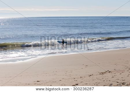 Surfer Watching The Waves On A Sandy Beach In The Morning On Santa Cruz Beach, California