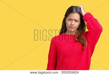 Young beautiful brunette woman wearing red winter sweater over isolated background confuse and wonder about question. Uncertain with doubt, thinking with hand on head. Pensive concept.