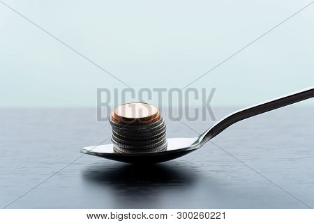 Single Metal Teaspoon With Silver And Bronze Coin Money Pile For Food Capitalism Business Concept Fi