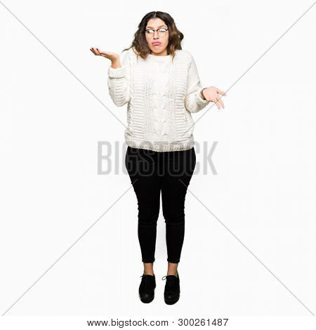 Young beautiful woman wearing glasses clueless and confused expression with arms and hands raised. Doubt concept.
