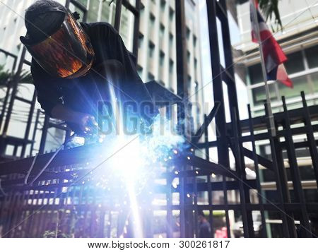 Welder On Steel Structure For Billboard Sign In Front Of The Hospital.