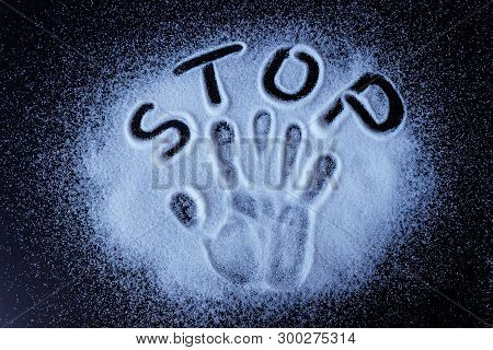 Salt, Sugar, Scattered On Black Surface. Written Word- Stop And Handprint.  Concept- Healthy Food, D