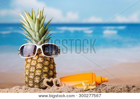 Sun Beach. The Concept Of Rest. Pineapple In Sunglasses In Sand And Cream For Sun Protection
