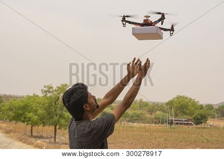 Concept Of Drone Delivery, Young Man Receiving The Product From Flying Drone