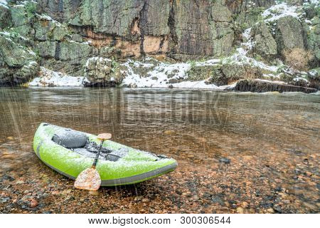 inflatable whitewater kayak with a paddle on shore of mountain river in springtime snowstorm - Poudre River in northern Colorado