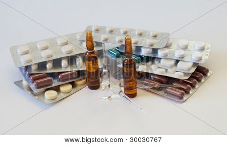 Multi-colored pills and ampules on the table