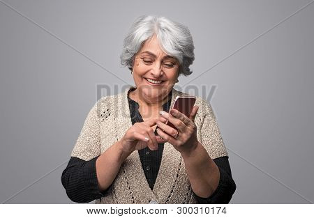 Beautiful Elderly Lady Laughing And Browsing Modern Smartphone While Standing Against Gray Backgroun