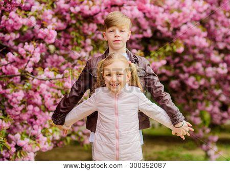 Couple Adorable Lovely Kids Walk Sakura Garden. Tender Love Feelings. Little Girl And Boy. Romantic