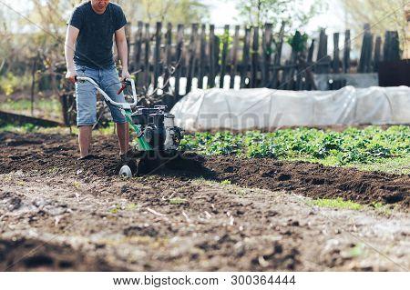 Young Farmer Gardener Cultivate Ground Soil Rototiller , Tiller Tractor, Cutivator, Miiling Machine,