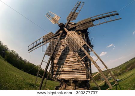 Wooden Windmill On The Hillside Against The Backdrop Of The Rural Landscape. Selective Focus.