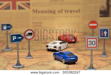 Travel concept. Toy car on vintage World map with road sign. Newspaper as a background. Closeup. Indoors. Smooth light. poster