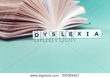 Dyslexia Word With An Open Book On Mint Background, Reading Difficulty And Disorder Concept. Educati