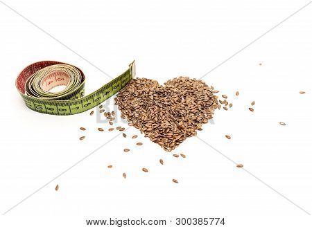 Measuring Tape And A Pile Of Flax Seeds In The Shape Of A Heart On A White Background