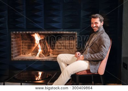 Handsome man sitting by a fireplace. poster