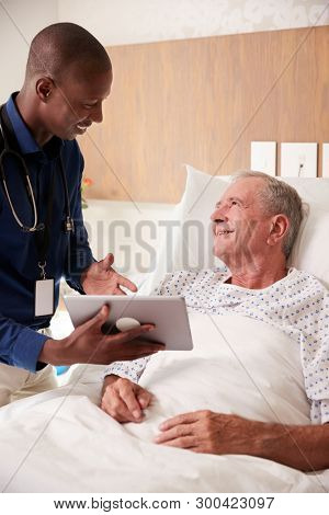 Doctor With Digital Tablet Visiting And Talking With Senior Male Patient In Hospital Bed