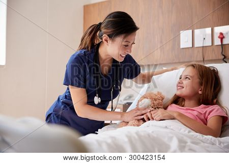Female Nurse Visiting Girl Lying In Hospital Bed Hugging Teddy Bear