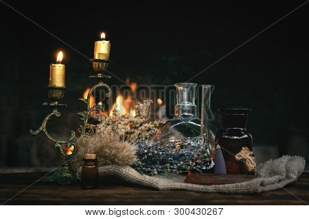 Alchemist Table. Magic Potion Bottles And Dried Herbs On A Table On A Burning Fire Background. Witch