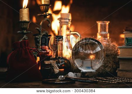 Crystal Ball, Magic Book, Magic Potion And Other Wizard Accessories On A Table On A Burning Fire Bac