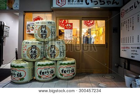 Kyoto, Japan, January 15 2019 : Stack And Decorate Of Japanese Liqueur (sake) Barrels Front Of Japan